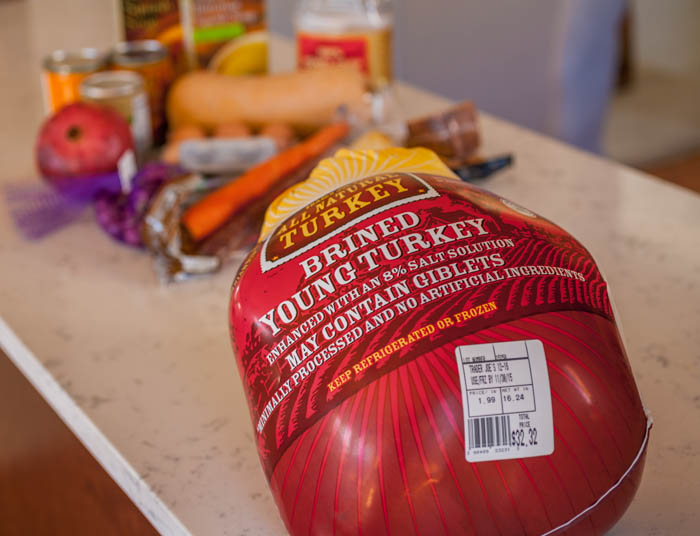 A brined, organic turkey sits in front of other Thanksgiving meal ingredients.