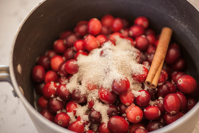 sugar and a cinnamon stick help sweeten and flavor cranberry coulis