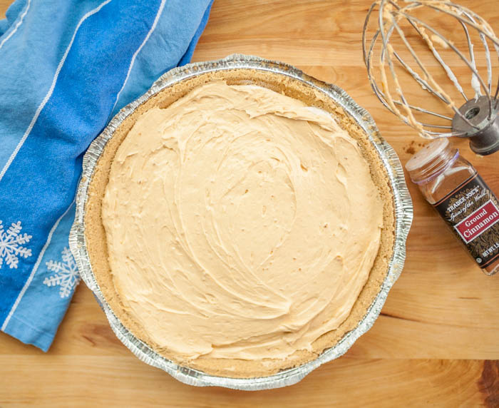 An easy to make no-bake pumpkin cheesecake on a cutting board with a wire whisk