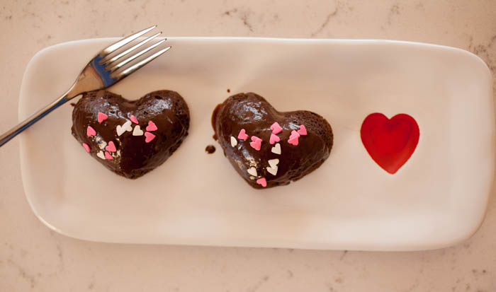 Two cakes glazed with ganache on a tray with a heart