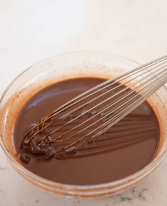 ganache in a glass bowl with a whisk