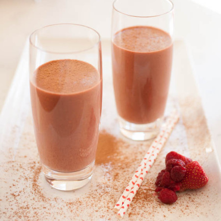 Two glasses of chocolate raspberry smoothie with heart straws, strawberries, and raspberries