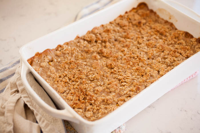 oatmeal with crisp topping in a white baking dish with a dish cloth