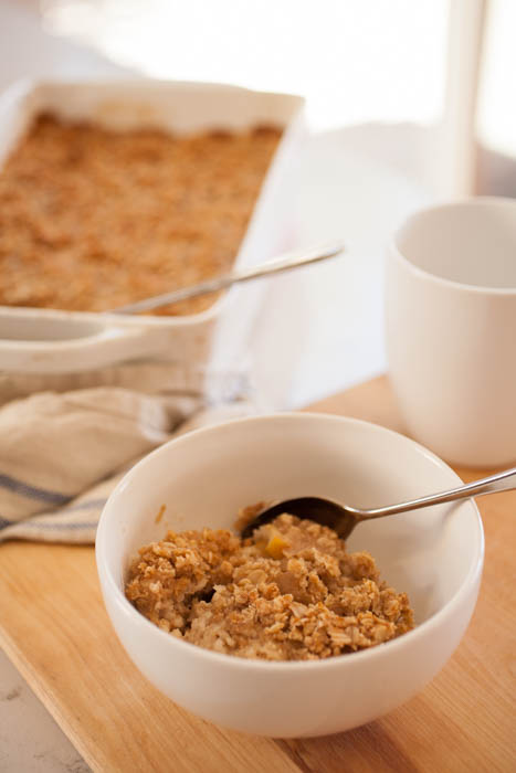 bowl of oatmeal crisp with coffee and oatmeal in baking dish behind.