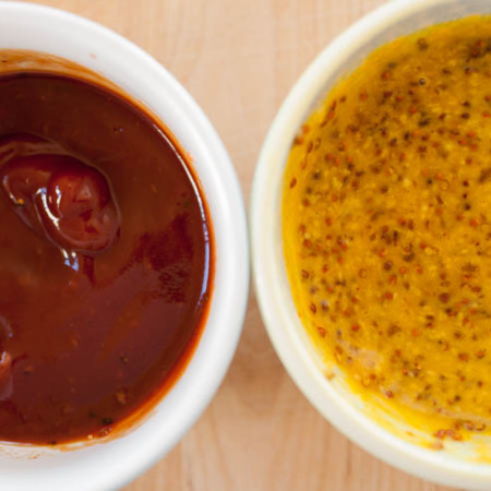 close-up of ketchup and honey mustard sauces to on a wooden cutting board