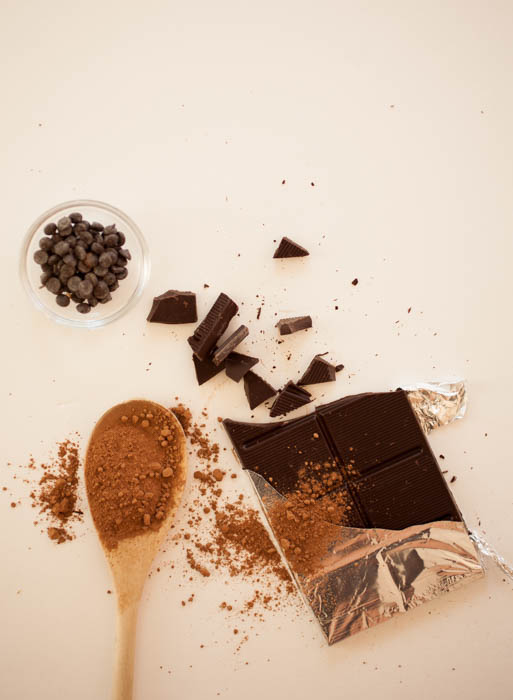 a spoon with cocoa, chocolate bar, and chocolate chips on a white background