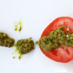 red tomato slices, green pesto on a white background