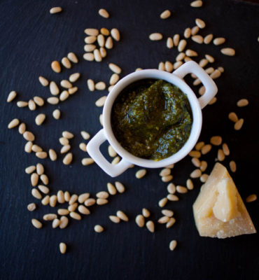 pesto in a white ramekin, pine nuts, and Parmesan cheese
