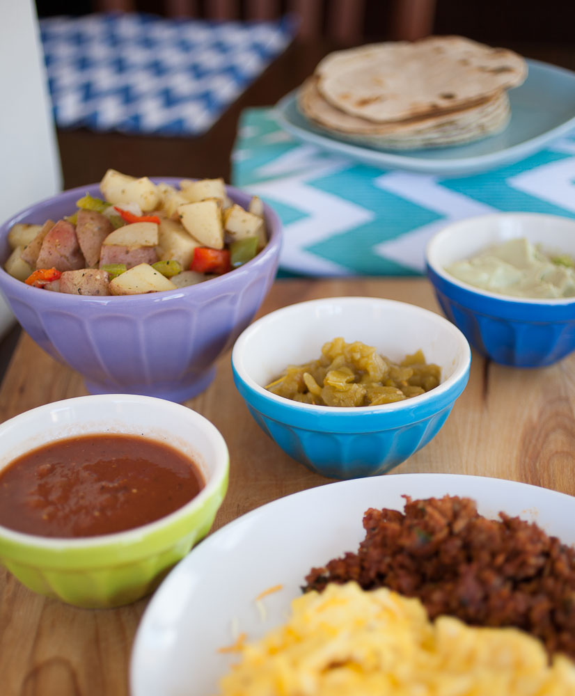 potatoes, green chile, salsa, avocado cream, and tortillas with chorizo and eggs in the foreground