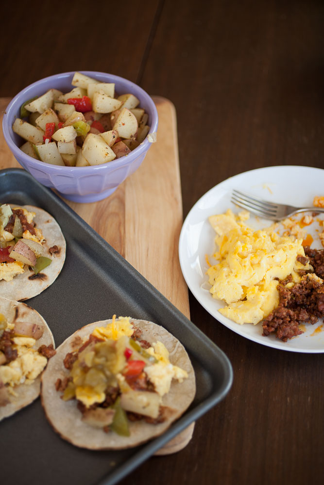 breakfast tacos with eggs and potatoes on a wooden board