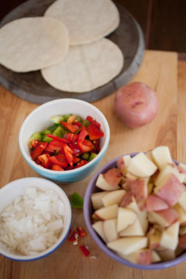 raw potatoes, onions, and bell peppers with tortillas in the background