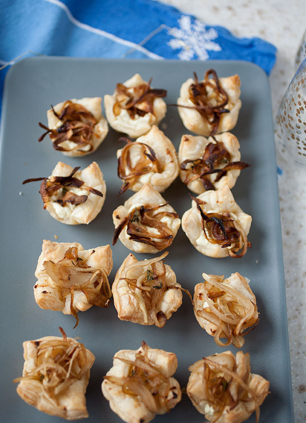 These caramelized onion and goat cheese tarts only require a handful of ingredients, aren't very labor intensive, and the sweet-savory flavors meld perfectly in the flaky pastry crust! These holiday appetizers will fly off the plate!