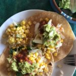 fish tacos with sautéed sweet corn on a white plate from Flurries of Flour