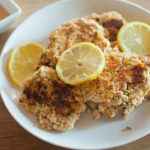 pan-fried salmon cakes on a plate with lemons and sauce