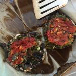 two mushrooms stuffed with veggies and black beans and topped with tomato sauce