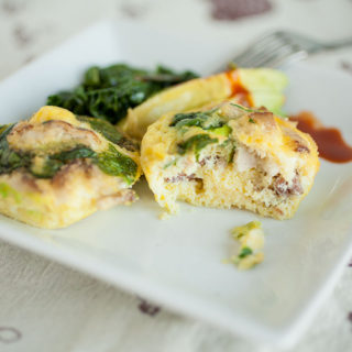 two egg bites on a plate with greens, avocado, and hot sauce.
